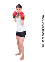 Serious young model in sportswear boxing while posing on...