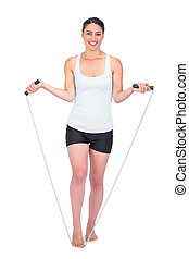 Smiling slender model jumping rope