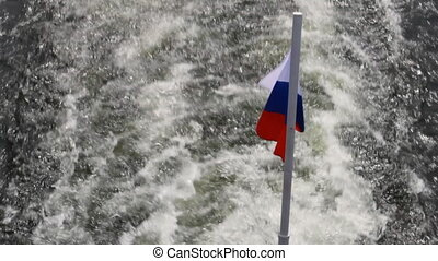 Passenger ship on river. - Flag of Russia. Waves following...