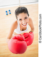 Fit woman wearing red boxing gloves smiling at camera at...