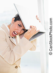 Crazed businesswoman hitting head off laptop looking at...
