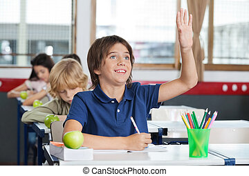 Schoolboy Raising Hand While Sitting At Desk - Happy little...