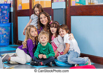 Teacher And Students Sitting Together On Floor - Portrait of...