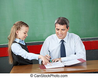 Girl Asking Question To Male Professor At Desk - Little girl...