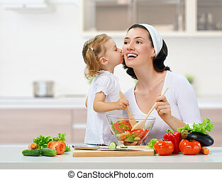 healthy food - mother and daughter prepare salads
