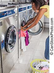 máquina, mulher, carregando, lavando, roupas