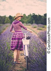 Woman in purple dress and hat with retro bicycle in lavender...