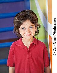 Cute Boy Smiling In Kindergarten - Portrait of cute little...