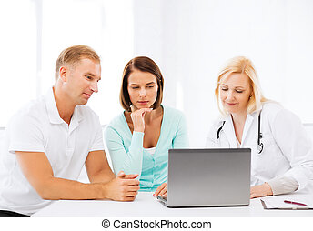 doctor with patients looking at laptop - healthcare, medical...