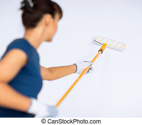 woman with roller and paint coloring the wall - interior...