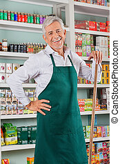 Senior Male Owner Standing Against Shelves In Store -...