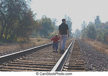 Boys walking on railroad tracks - Big brother walking little...