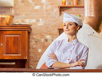 Young woman cook - Image of young woman cook standing at...
