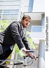 Caucasian businessman riding a bike