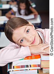 Happy Schoolgirl Leaning On Stack Of Books