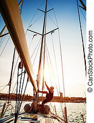 Young sailor on sailboat - Young sailor working on sailboat,...