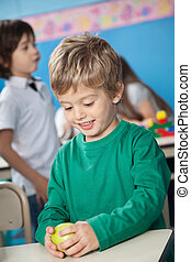 Boy Holding Smith Apple With Classmate In Background - Happy...