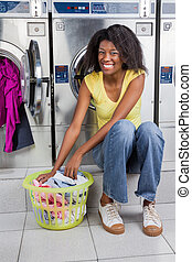 Woman With Basket Of Clothes In Laundry