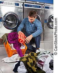 Man Putting Dirty Clothes In Basket at Laundromat - Young...