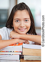 Schoolgirl Leaning On Stack Of Books In Classroom
