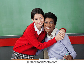 Happy Schoolgirl Hugging Professor In Classroom - Portrait...