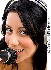 close up of young woman with headphone and microphone on an isolated white background