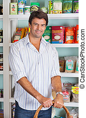Portrait Of Man With Basket In Grocery Store
