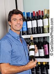 Portrait Of Man Showing Alcohol Bottle - Portrait of mid...