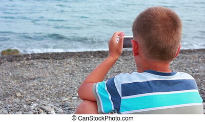 Boy on Beach with Phone - boy playing on the seashore...