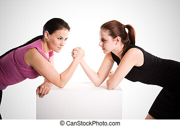 Two businesswomen arm wrestling - An shot of two...