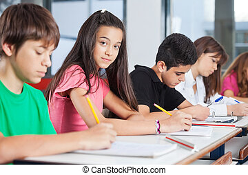 Teenage Girl Sitting With Classmates Writing At Desk -...