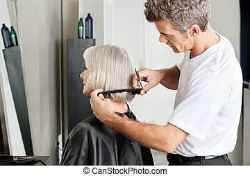 Hairdresser Examining Hair Length Of Client - Side view of...