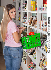 Woman With Shopping Basket In Supermarket