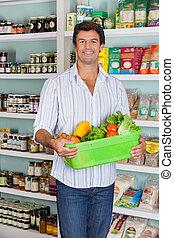 Man Holding Basket Of Vegetables In Supermarket