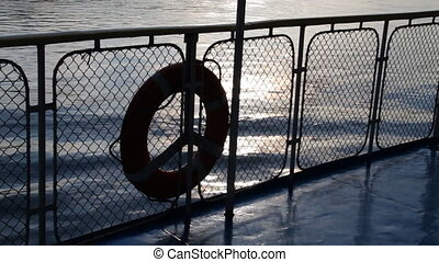 Passenger ship. - Water surface, reflections. Life buoy.