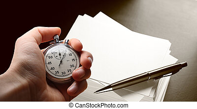 Hand holding stopwatch, stack of paper cards and pen