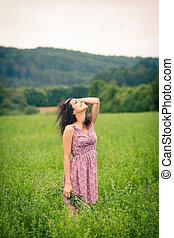 Beautiful young woman enjoying fresh air outdoors in a...