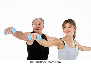 fitness - senior man and young woman exercising in gym....