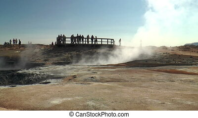 tourists watching fumaroles and mud pools in iceland at...