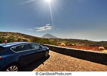 Blue car on a roadside near mountain foot
