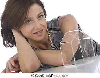 portrait of 40s woman looking at a transparent little house