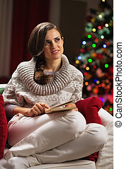 Thoughtful young woman sitting in armchair near christmas...