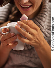 Closeup on young woman eating marshmallow from cup of hot...