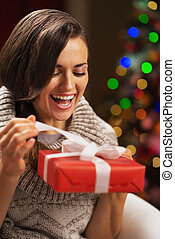 Happy young woman opening present box in front of christmas lights