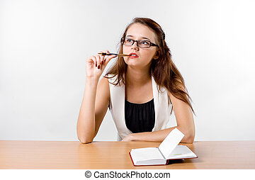 thinking business lady in glasses sitting at her desk -...