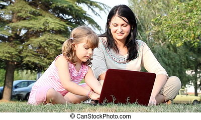 child and girl with laptop - child and girl sitting on grass...