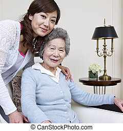 mother and daughter - senior asian woman and her adult...
