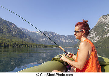 Woman in boat, fishing on the lake