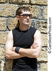 Young man in sunglasses standing near a wall 2