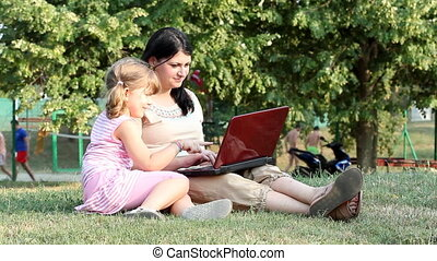 girl and child typing on laptop
